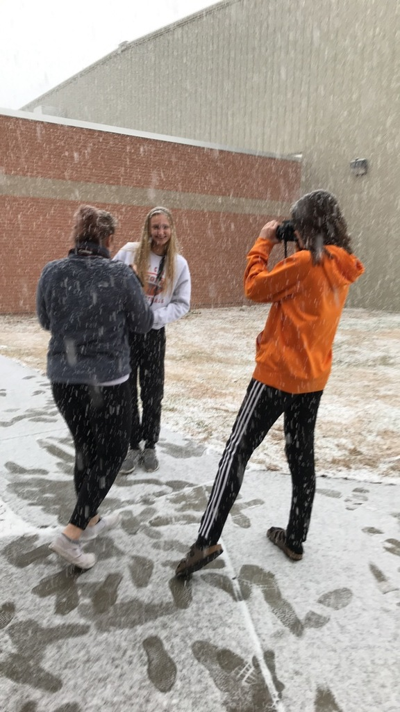 students outside taking photos during snow